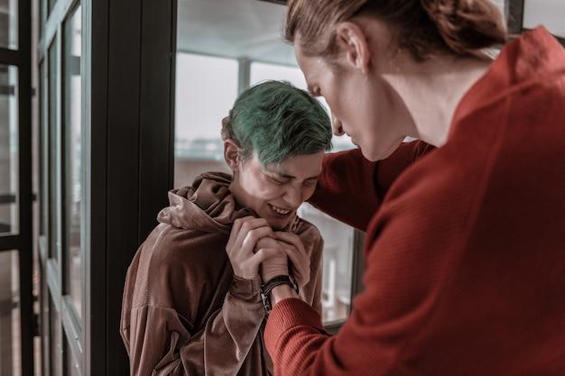 Niezwykle przerażony. zielonowłosa dziewczyna bardzo się boi agresywnego szalonego chłopaka