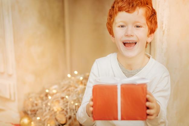 Niezwykle szczęśliwy rudowłosy dzieciak z szeroko otwartymi ustami, podekscytowany otrzymaniem prezentu bożonarodzeniowego.
