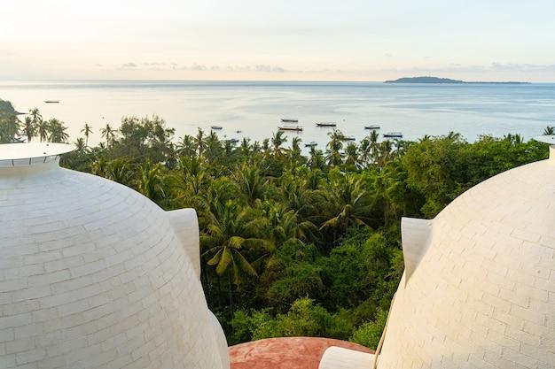 Niezwykły budynek z okrągłymi dachami nad zielonymi palmami nad brzegiem morza