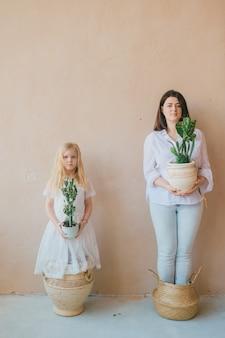 Niezwykły dziwny portret życia rodzinnego. dziwna dorosła matka stoi ze swoją śmieszną córeczką w studiu i trzyma w rękach garnki z roślinami.