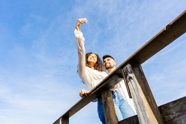 Niezwykły kąt widzenia strzał wielorasowe para na drewnianym moście plaży przy selfie na wakacjach w nadmorskim kurorcie. duża przestrzeń do kopiowania nieba idealna na banery lub reklamy. latynoska dziewczyna używająca smartfona