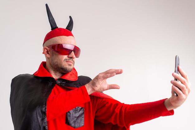 Niezwykły kaukaski mężczyzna w czerwonych okularach przeciwsłonecznych, czarnoczerwonym kostiumie na halloween i kapeluszu z diabelskimi rogami, pokazując gesty dłoni na smartfonie w dłoni.