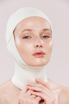 Niezwykły obraz modelki w studio dziewczyna w bandażach na białym tle różowym tle