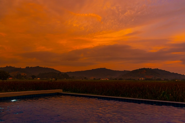 Niezwykły pomarańczowy ognisty zachód słońca w tropikach. widok z basenu na pole ryżowe i góry