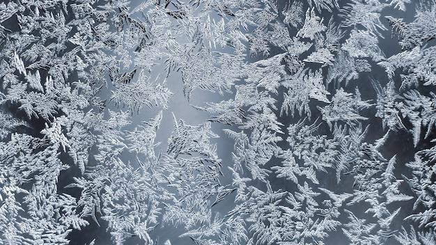 Niezwykły szron na zimowym oknie. kreatywność sezonowości