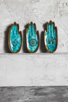 Niezwykły turkusowy talerz w kształcie dłoni na szarym tle. motyw etniczny