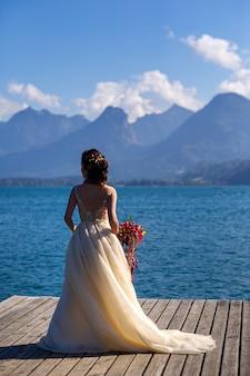 Niezwykły wydłużony bukiet ślubny w rękach panny młodej.