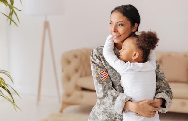 Nigdy nie pozwolę ci odejść. przywiązany do krzywdzenia namiętnej matki i jej córki, przytulających się mocno i cieszących się spotkaniem po tym, jak mama spędziła kilka miesięcy na obozie szkoleniowym