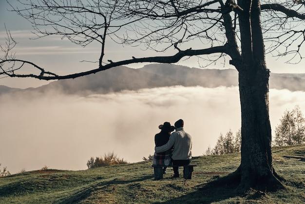 Nigdy nie pozwolę ci odejść! widok z tyłu młodej pary cieszącej się doskonałym widokiem na pasmo górskie podczas siedzenia na ławce