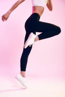 Nigdy nie przestawaj przycięte zdjęcie sportowej młodej kobiety w czarnych legginsach skaczącej na różowym tle