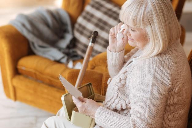 Nigdy nie zapomnę. smutna, smutna, nieszczęśliwa kobieta trzymająca list i płacząca, mając nostalgiczne wspomnienia ze swojej przeszłości