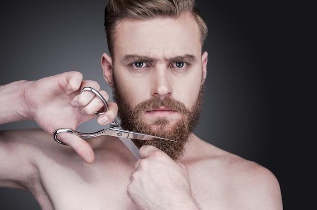 Nigdy więcej brody. portret przystojnego, młodego mężczyzny bez koszuli, tnącego brodę nożyczkami i patrzącego na kamerę, stojąc na szarym tle