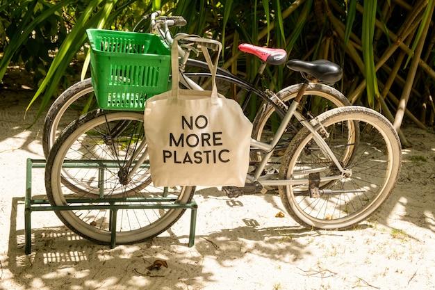 Nigdy więcej plastikowa torba ekologiczna na koszyku rowerowym zaparkowanym na piaszczystym tropikalnym lesie
