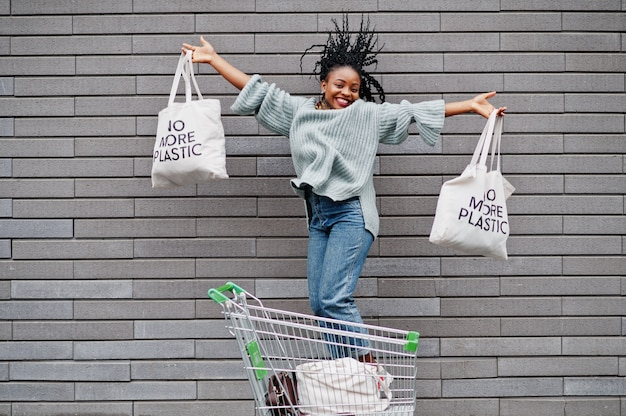 Nigdy więcej plastiku. afrykańska kobieta z wózek na zakupy tramwajem i eco torbami skacze plenerowego rynek.