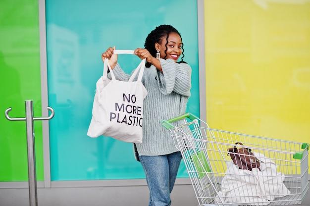 Nigdy więcej plastiku. afrykańska kobieta z wózek na zakupy tramwaju przedstawienia eco torbą pozuje plenerowego rynek.