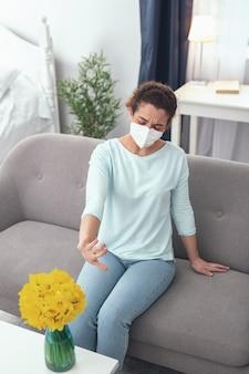Nigdy więcej pyłków. młoda jasnowłosa chora dziewczyna marszczy czoło w masce ochronnej, która zapobiega uczuleniu na pyłki kwiatów