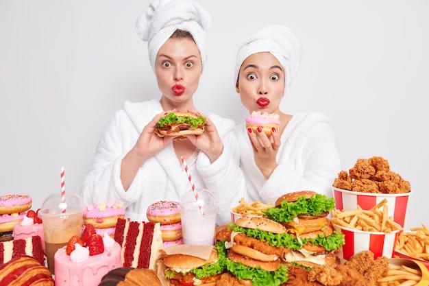 Nigdy wystarczająco. dwie głodne modelki w szatach spożywają niezdrowe jedzenie, trzymają czerwone usta zaokrąglone w pozie z burgerem i pączkiem, stojąc przy stole pełnym cheat mealów.