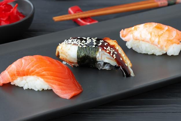 Nigiri sushi z łososiem i krewetką podane na czarnym talerzu ceramicznym