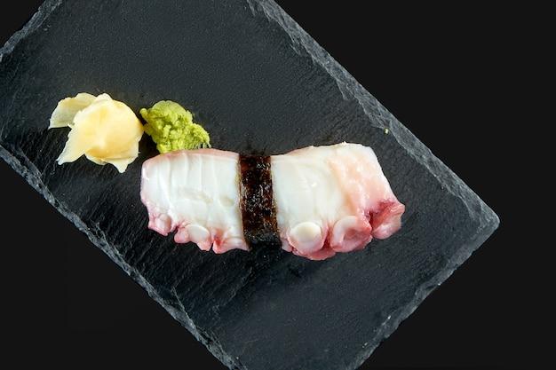 Nigiri sushi z ośmiornicą na czarnej desce z imbirem i wasabi. kuchnia japońska. dostawa jedzenia. pojedynczo na czarno