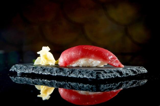 Nigiri sushi z tuńczykiem na czarnej desce z imbirem i wasabi. kuchnia japońska. dostawa jedzenia. pojedynczo na czarno
