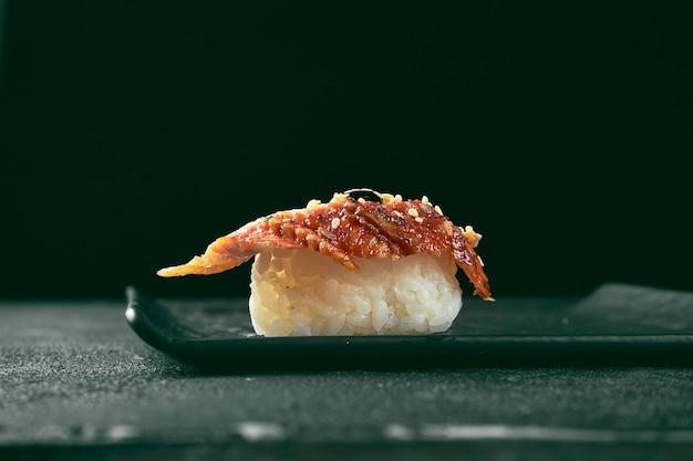 Nigiri sushi z węgorzem na czarnej desce z imbirem i wasabi. kuchnia japońska. dostawa jedzenia. czarne tło