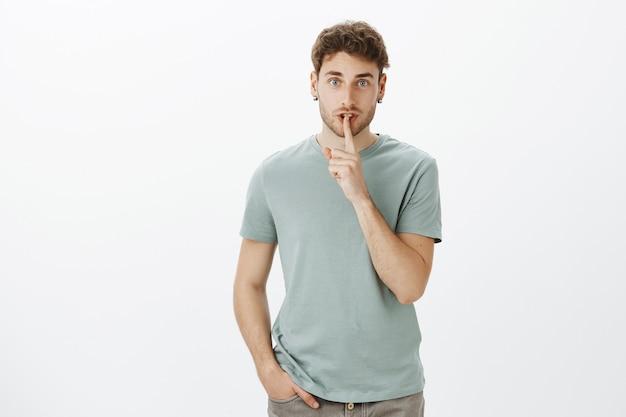 Nikt nie powinien, nie trzymaj buzi na kłódkę. portret czarującego, pewnego siebie europejczyka w t-shircie, mówiącego ciii, pokazującego gest uciszenia z palcem wskazującym na ustach