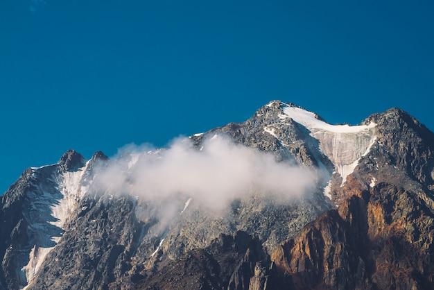 Niska chmura przed pasmem górskim. lodowiec pod jasnym niebieskim niebem. śnieżny szczyt w słoneczny dzień. gigantyczna skalista grań ze śniegiem. klimatyczny, minimalistyczny krajobraz górski o majestatycznej naturze.