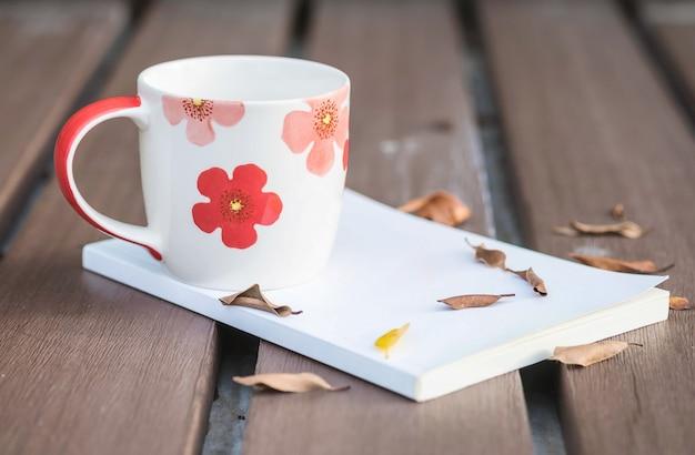 Niska kluczowa fotografia piękna filiżanka kawy na białej książce na drewnianym stole z wysuszonymi liśćmi z ciemnym brzmieniem i wybór skupia się