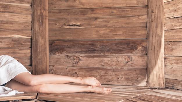 Niska sekcja kobiety lying on the beach na drewnianej ławce przy sauna