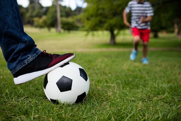 Niska sekcja ojca i syna grających w piłkę nożną