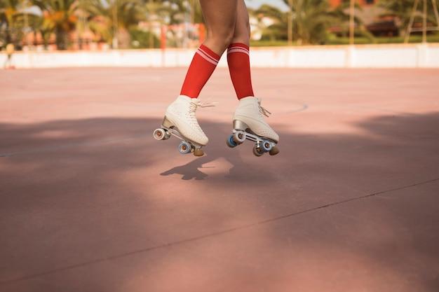 Niska sekcja żeńska jest ubranym biała rolkowa łyżwa skacze w powietrzu