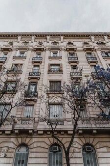 Niski kąt betonowego budynku w mieście z drzewami
