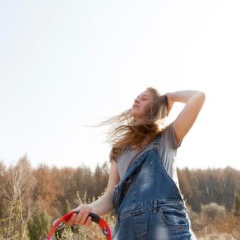 Niski kąt beztroski kobiety w przyrodzie gospodarstwa tamburyn