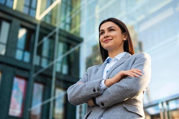 Niski kąt bizneswoman z rękami skrzyżowanymi w mieście