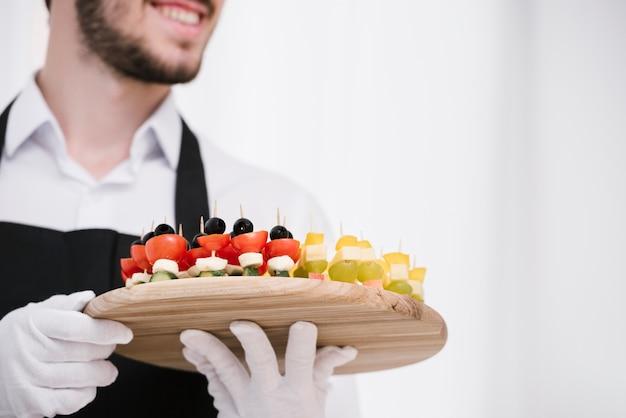 Niski kąt brodaty kelner gospodarstwa przekąski