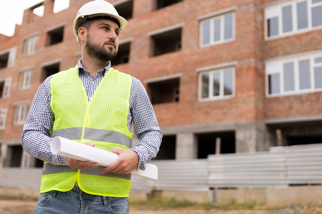 Niski kąt budowniczy mężczyzna trzyma projekt