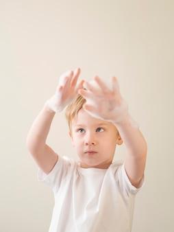 Niski kąt chłopiec z pianką do kąpieli na rękach