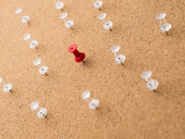 Niski kąt czerwona szpilka otoczona białymi szpilkami na desce