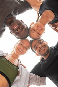 Niski kąt czterech młodych sportowców międzykulturowych w odzieży sportowej, patrzących na ciebie, dotykających głowy