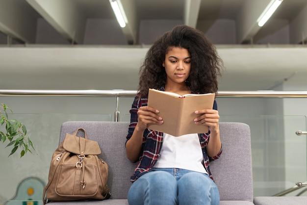 Niski kąt dziewczyna na kanapie czytania