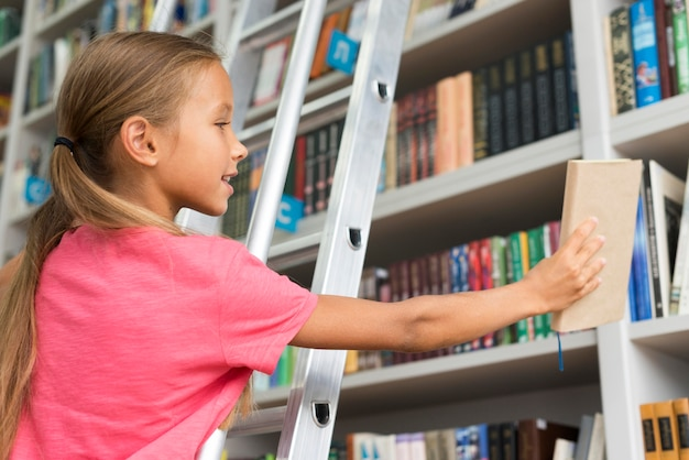 Niski kąt dziewczyna umieszcza książkę na półce
