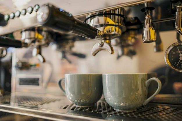 Niski kąt ekspresu do kawy z filiżankami