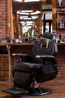 Niski kąt fryzjerski ze skórzanym krzesłem