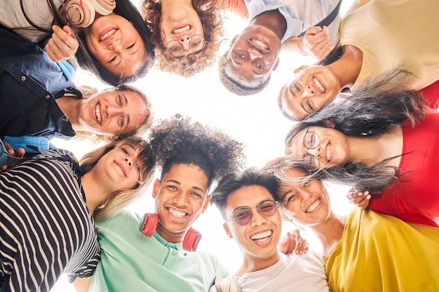 Niski kąt grupy studentów to razem szczęśliwe i uśmiechnięte twarze młodych nastolatków patrzących na ...