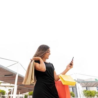 Niski kąt kobieta patrzeje smartphone