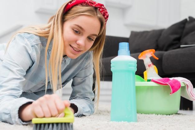 Niski kąt kobieta szczotkuje dywan