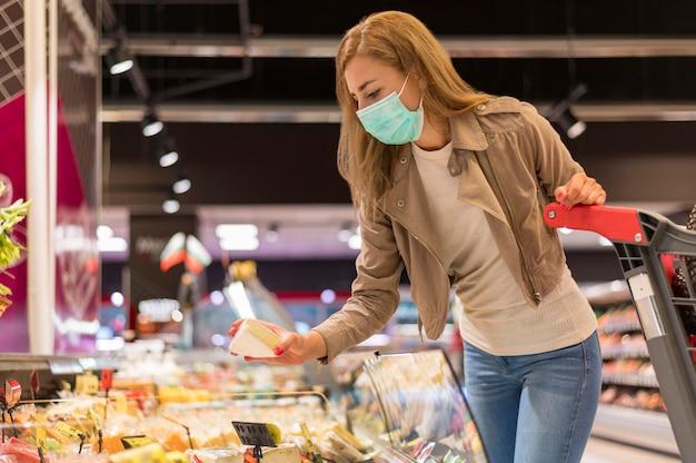 Niski kąt kobieta z maską na zakupy
