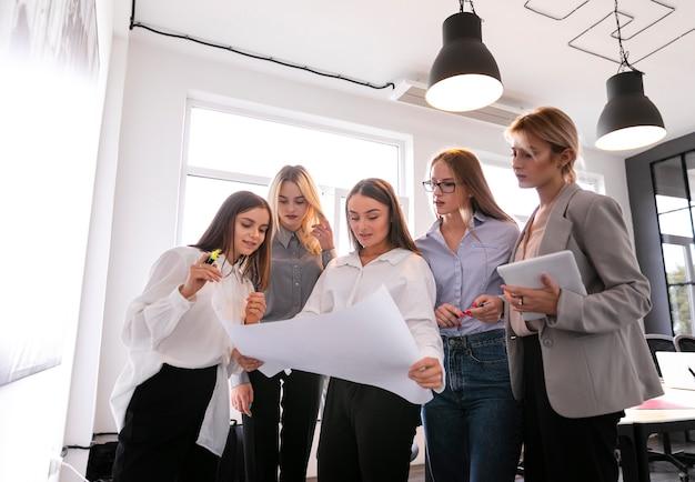 Niski kąt kobiety korporacyjne sprawdzanie planów
