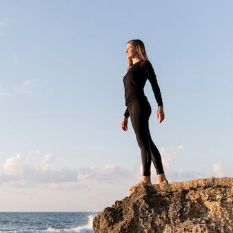 Niski kąt kobiety stojącej i patrząc na morze