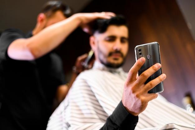 Niski kąt kostiumer w sklepie fryzjer patrząc na telefon